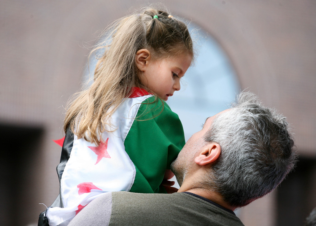 Three-year-old Jenna wears the Syrian flag as a dress while being carried by her father during the first Refugees Welcome rally in Ottawa on September 5, 2015. Captis Photos/ Jaclyn McRae-Sadik